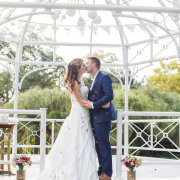 arch, confetti, bride & groom, suit - Katie Mayhew Photography