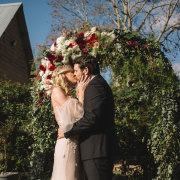 bride and groom, bride and groom, floral arch, kiss, kiss - Planned To Perfection
