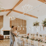 bride and groom, bride and groom, chandeliers, hanging decor, kiss, kiss, naked bulbs - The Venue @ Pearl Mountain