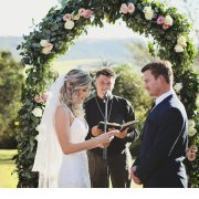 bride and groom, bride and groom, floral arch, minister, outside ceremony